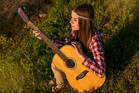 woman in red and white checked sport shirt holding dreadnought brown acoustic guitar
