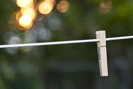 tilt shift photo of brown wooden clip on white string