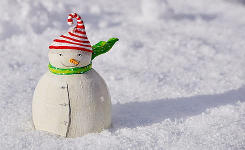 white snowman on snow during daytime