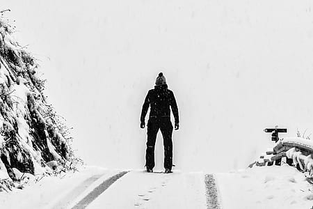 Man Standing on White Snow Covered Ground Beside Mountain