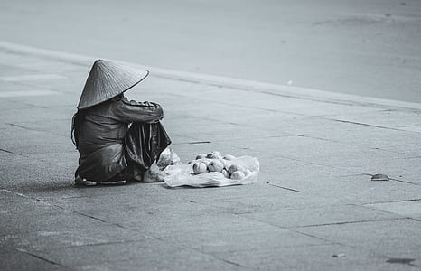 grayscale photo of a person sitting on gray road