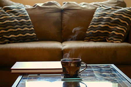 brown ceramic teacup on glass-top coffee table beside brown sofa