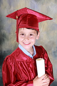 boy wearing red academic gown with mortar board
