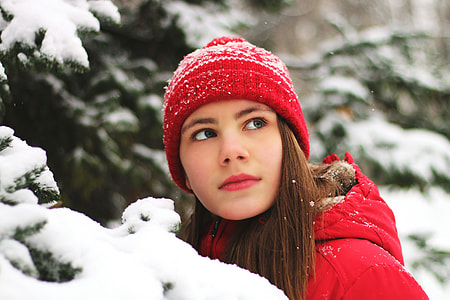 Girl wearing hat in winter snow and ice