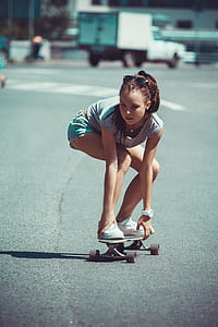 girl in white shirt and teal shorts riding skateboard at daytime