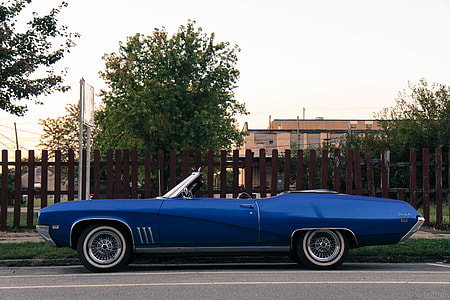 parked blue convertible hood car beside brown wooden fence