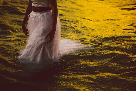 woman wearing dress walking on body of water