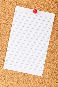 black lined paper pinned on cork board