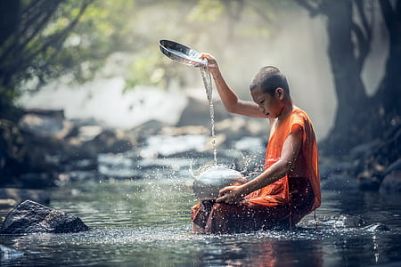 shallow focus photography of monk pouring water on silver pot at river