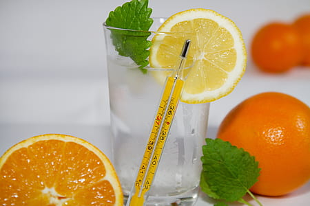 yellow thermometer beside glass of water with sliced lemon