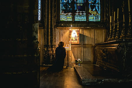 person kneeling inside cathedral