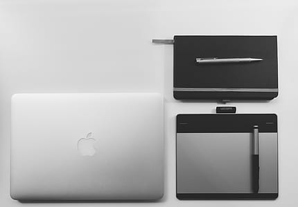 silver MacBook beside pentab