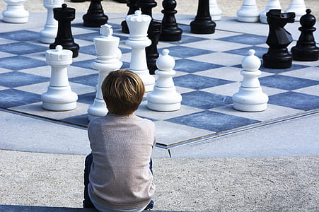 boy sitting watching white and black giant chess board