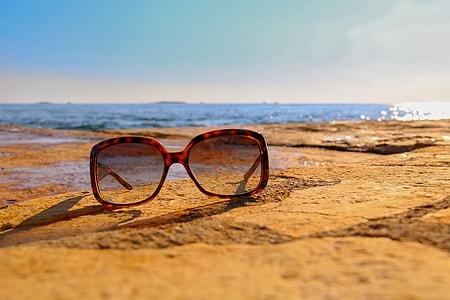 tortoiseshell framed sunglasses on brown sand