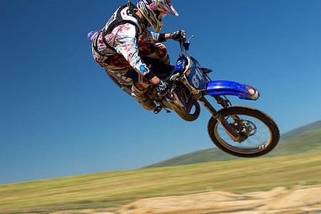 man riding a blue dirt bike