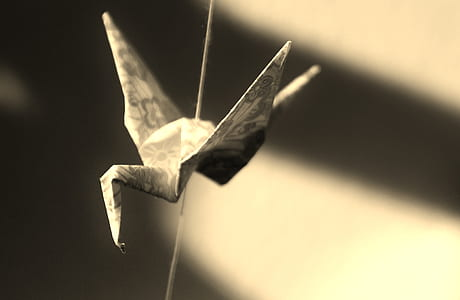selective focus photography of grey crane origami
