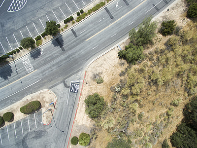 aerial photography of gray road near green grass and trees during daytime