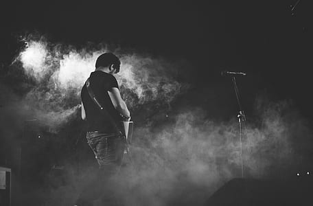 man standing on stage with white smokes photography