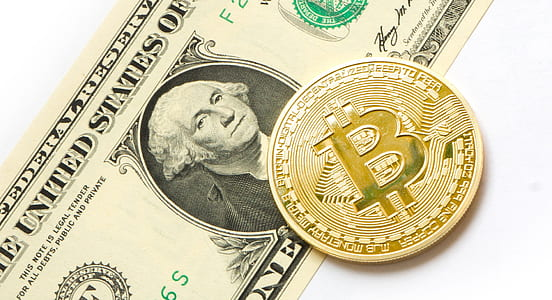 Bitcoin on top of U.S. dollar banknote
