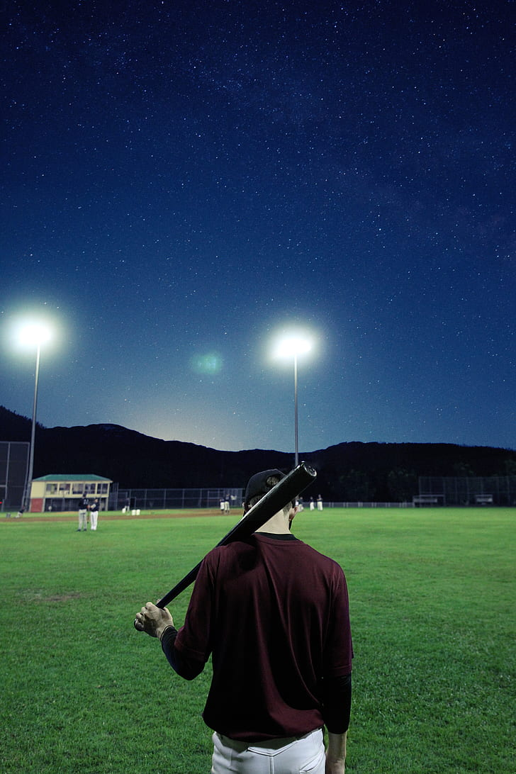 man holding baseball bat on baseball field during nighttime