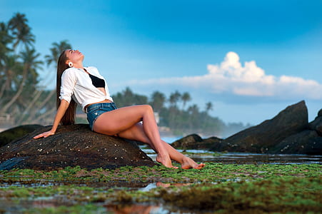 Woman Lying on Rock Against Sky