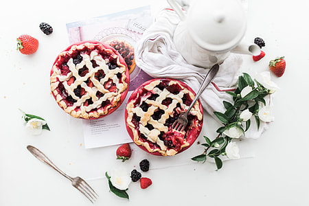 food photography of two pies with two stainless steel forks near teapot on table