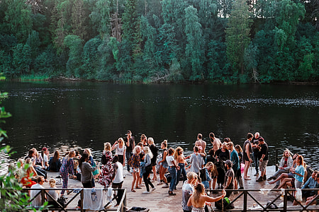 people gathered near lake surrounded by green trees