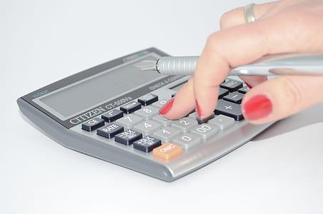 person pressing button on desk calculator