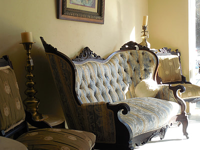 loveseat with beside sofa chair and near candle holder with candle