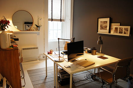 square brown wooden desk and flat screen monitor