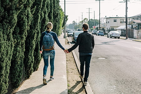 woman and man walking on sidewalk while holding hands