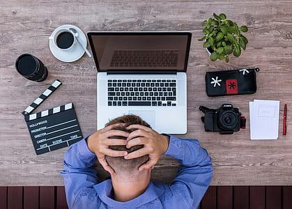closeup photo of man facing gray laptop on table