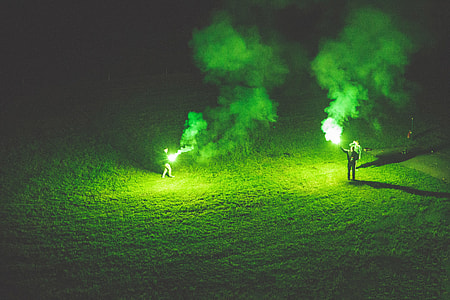 People holding green flares at night