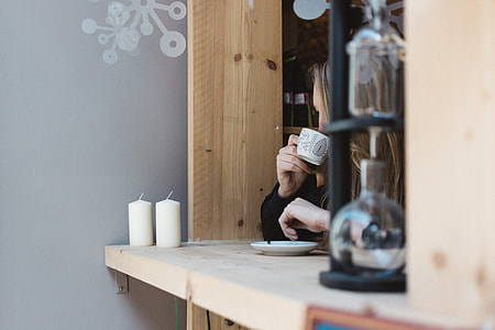 Girl drinking coffee at a window seat