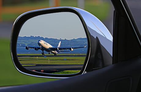 vehicle wing mirror reflect view of airliner about to fly during daytime