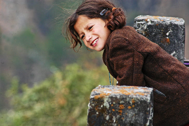 Girl Wearing Brown Coat Leaning On Concrete Pillar