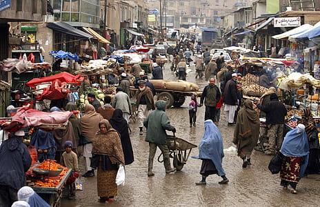 people wearing capes walking on street near market
