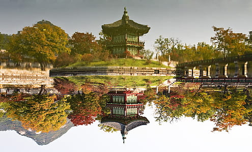 red and green temple near body of water