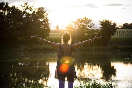 woman wearing black sleeveless top during sunset
