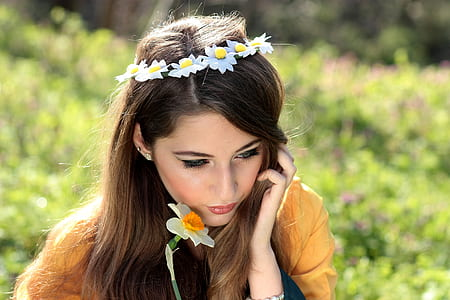woman holding a white daffodil wearing flower headdress selective-focus photo