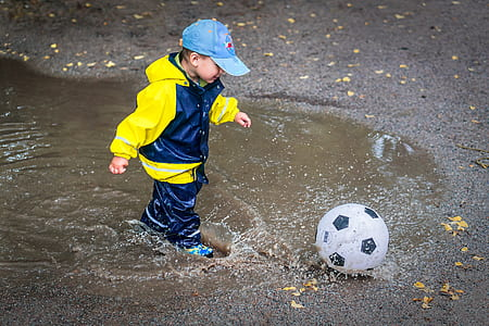 boy playing soccer ball during daytime