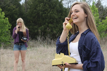 smiling woman holding yellow desk phone