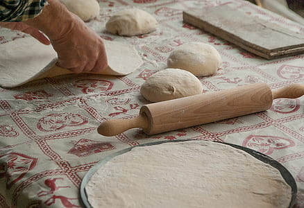 person holds dough near brown wooden rolling pin