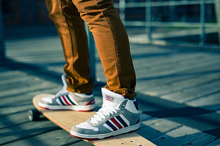 person wearing gray-white-and-red high-top sneakers on beige longboard