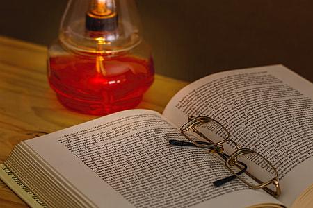 eyeglasses on a book near on fragrance bottle