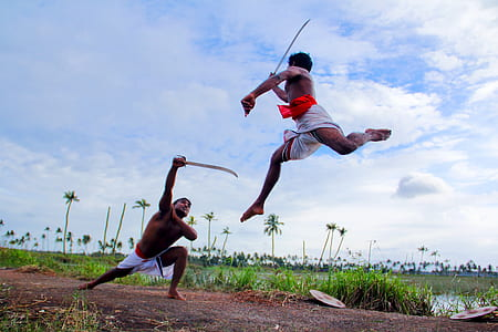 two person fencing swords during daytime