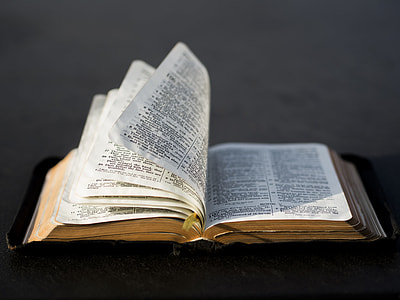 selective focus photography of open bible with black leather cover