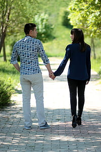 man and woman holding hands walking on road