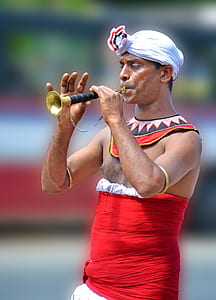 man playing brass flute at daytime