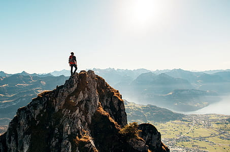 man standing on cliff at daytime